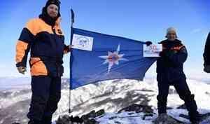 Спасатели Дальневосточного регионального отряда развернули флаг МЧС России на вершине горы Элеор